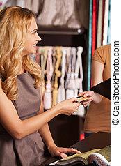 bello, biondo, ragazza, dare, credito, card., attraente, donna stando piedi, in, negozio, e, sorridente