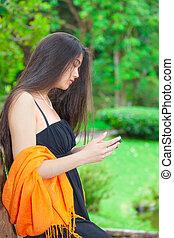 bello, biracial, ragazza adolescente, usando, cellphone, con, fogliame, in, fondo