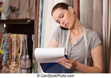 bello, brunetta, parlando telefono, e, writing., attraente, donna stando piedi, in, drappeggio, negozio