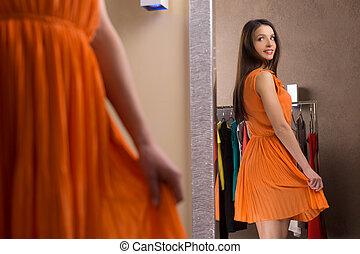 bello, dress., attraente, giovane, in, arancia, vestire, guardando, il, specchio, e, sorridente