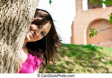 bello, giovane, nascondendo dietro, uno, albero