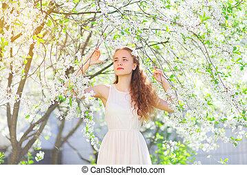 bello, giovane ragazza, con, capelli ricci, in, primavera, fioritura, giardino