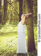 bello, giovane, sposa, in, matrimonio bianco, vestire, inclinandosi, albero, fuori