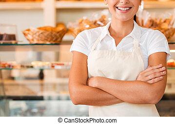 bello, grembiule, primo piano, donna, baker., negozio, custodia, giovane, panetteria, standing, mentre, braccio attraversarono, felice