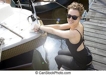 bello, ragazza, in, occhiali da sole, seduta, su, uno, banchina, appresso, il, barca, in, il, luce sole