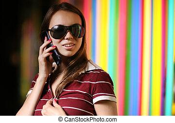 bello, ragazza, in, occhiali da sole, talkng, su, telefono cellulare