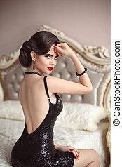 bello, tramortire, elegante, signora, in, nero, brillare, sequins, vestire, seduta, su, lusso, divano, in, moderno, interior., moda, gemme, gioielleria, set., brillante rosso, labbra, hollywood, fare, su.