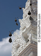 Bells on a carved white tower in a Buddhist temple