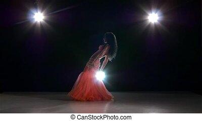 Belly dance of beautiful girl, on black, back light, slow motion
