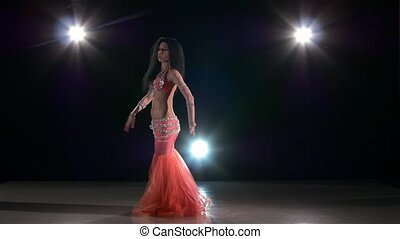 Belly dance of sexy woman in shiny pink dress, on black, back light, slow motion