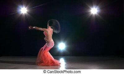 Belly dance woman bellydancer dancing on black, back light, slow motion