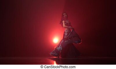Belly dancer arabian in exotic dress dancing. Red smoke...