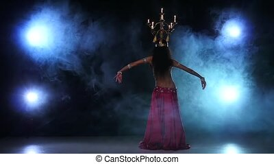 Belly dancer continue dancing with candles, her head, black, smoke, slow motion
