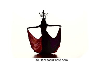 Belly dancer dancing with burning candles on her head, silhouette, slow motion, on white