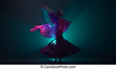 Beautiful exotic belly dancer girl continue dance uses fans. Smoke background. Slow motion