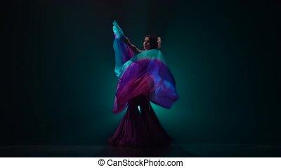 Belly dancer girl continue dance uses fans. Smoke...
