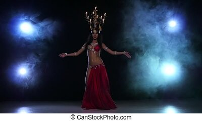 Belly dancer girl continue dancing with candles, her head, black, smoke, slow motion