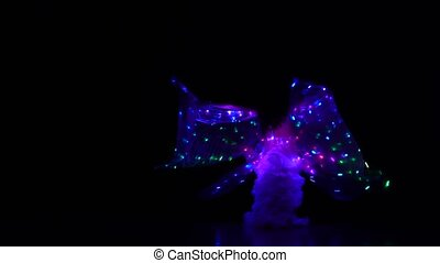 Belly dancer girl dance with two glowing lights wings. Black...