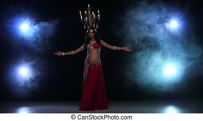 Belly dancer girl go on dancing with candles, her head, black, smoke, slow motion
