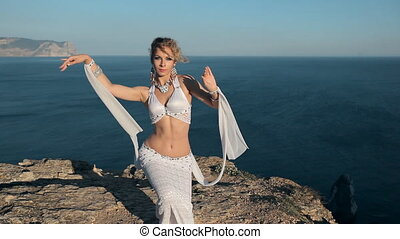Belly dancer girl on the rock in Crimea near Black sea