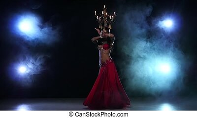 Belly dancer girl starts dancing with candles, her head, black, smoke, slow motion