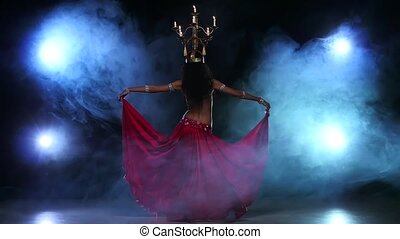 Belly dancer go on dancing with candles, her head, black, smoke, slow motion