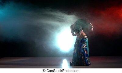 Belly dancer in a blue stage costume dancing in smoke, on red, blue, slow motion