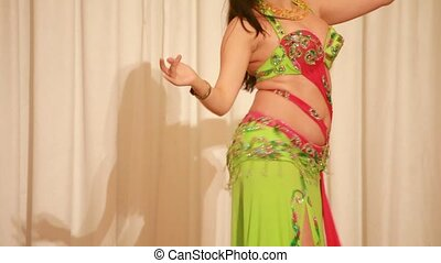 Belly dancer in green perform during photo session in studio