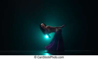 Belly dancer who is starting shaking her hips. Smoke...