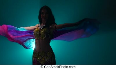 Belly dancer with a veil in her hands . Smoke background....