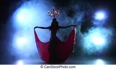 Belly dancer woman dancing with candles on her head, on black background, smoke, slow motion, silhouette