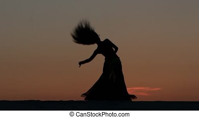 Belly dancing against the beautiful sunset on the beach. Silhouettes
