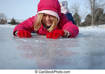 Belly Down on Ice - Young girl prone on the ice during...