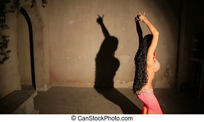 Bellydancer in red dress with shadow.
