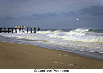 The fishing pier and beach with stormy seas in Belmar, New Jersey.
