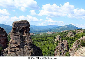 Belogradchik rocks formation in the forest against clear blue sky in summer