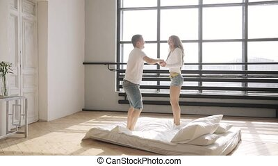 Beloved are jumping in bed holding hands in their new flat....