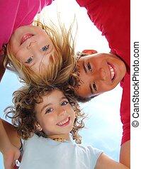 Below view of happy three children embracing hug each other...