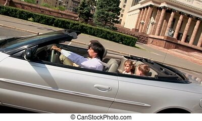 Belt up family ride in cabriolet by street near huge architectural complex at sunny summer day