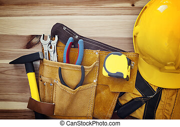 Belt with tools and yellow helmet on wood