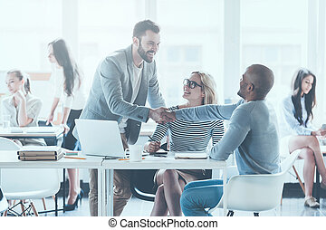 bem-vindo, ligado, board!, dois, alegre, homem jovem, apertar mão, enquanto, sendo, em, escritório, junto, com, seu, colegas
