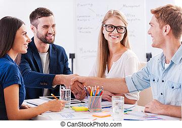 bem-vindo, ligado, board!, grupo, de, alegre, pessoas negócio, sentar tabela, junto, enquanto, dois homens, apertar mão, e, sorrindo