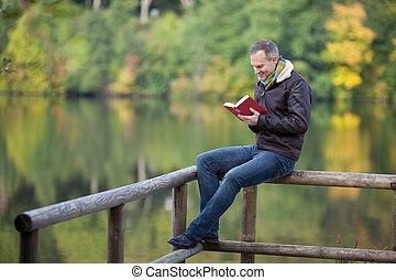 bemannen lees, boek, terwijl, zittende , op, omheining,...