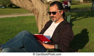 bemannen lees, een, boek, in het park