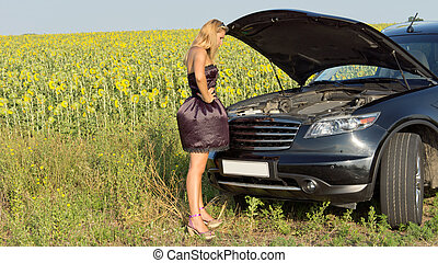 Bemused woman looking at car engine