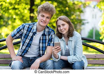 bench., été, sien, school., repos, parc, couple, tient, boy., jeune, émotions, après, pleasure., smartphone., étudiant, mains, close-up., fille souriante, bonheur, heureux