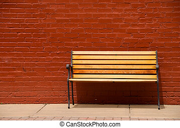 Bench - A bench beside a red brick wall.