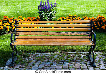 Bench - A bench in the park, next to floral arrangements.