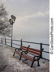 bench and lantern on foggy winter morning. location...
