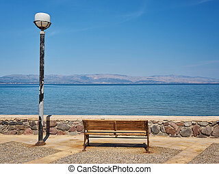 bench and lantern on the embankment of the sea